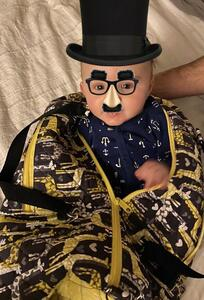 baby in groucho disguise inside a duffel bag